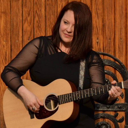 Stacia Abernatha performing with guitar